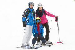 有一个孩子的年轻愉快的家庭,滑雪在山 库存图片