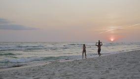 有一个孩子的幸福家庭在度假在海滩的在日落4k 股票录像