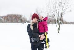 有一个孩子的愉快的年轻母亲冬天步行的 免版税库存图片