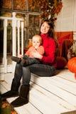 有一个孩子的美丽的少妇与pumpk的前沿的 库存图片