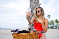 有一个完善的图的少妇站立与她减速火箭的自行车在绿草的公园,当享受休息时在乘坐以后 免版税库存图片