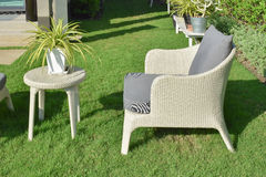 有一个室外家具休息室小组的绿色庭院与藤条椅子 免版税图库摄影