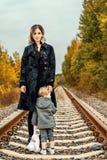 有一个小儿子的一个年轻母亲路轨的在风暴前的森林里 图库摄影