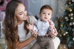 有一个小儿子的妈妈在一棵美丽的圣诞树附近在他的房子里 免版税库存照片