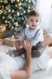 有一个小儿子的妈妈在一棵美丽的圣诞树附近在他的房子里 库存图片
