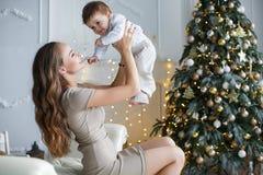 有一个小儿子的妈妈在一棵美丽的圣诞树附近在他的房子里 免版税图库摄影