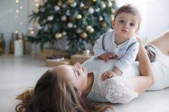 有一个小儿子的妈妈在一棵美丽的圣诞树附近在他的房子里 库存照片