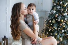 有一个小儿子的妈妈在一棵美丽的圣诞树附近在他的房子里 图库摄影
