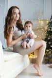 有一个小儿子的妈妈在一棵美丽的圣诞树附近在他的房子里 免版税库存图片