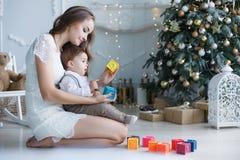 有一个小儿子的妈妈在一棵美丽的树附近在他的使用与色的立方体的房子里 免版税库存照片