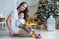 有一个小儿子的妈妈在一棵美丽的树附近在他的使用与色的立方体的房子里 库存照片