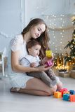 有一个小儿子的妈妈在一棵美丽的树附近在他的使用与色的立方体的房子里 库存图片