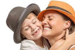 有一个小儿子的妈妈笑的帽子的拥抱和,逗人喜爱的家庭 库存图片