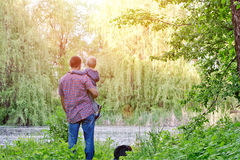 有一个小儿子的爸爸在森林湖,背面图的岸站立 库存图片