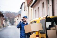 有一个小包箱子的送货人在街道上 免版税库存图片