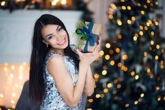 有一个小圣诞节礼物的性感的妇女 一件短的礼服的美丽的女孩坐在地板上的格子花呢披肩 明亮和 免版税图库摄影
