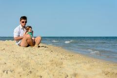 有一个小女儿的一个父亲坐海滩在海的背景 免版税库存图片