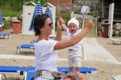 有一个小女儿的妈妈海滩的 免版税库存图片