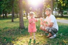 有一个小女儿的愉快的父亲日落吹的肥皂泡的在夏天公园户外 免版税库存照片