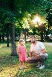 有一个小女儿的愉快的父亲日落吹的肥皂泡的在夏天公园户外 免版税库存图片