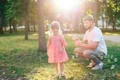 有一个小女儿的愉快的父亲日落吹的肥皂泡的在夏天公园户外 库存图片