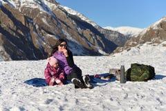 有一个小女儿的母亲在一顿野餐的冬天在山 库存照片