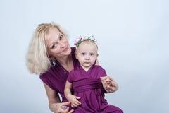 有一个小女儿的白肤金发的妇女匹配的穿戴 免版税库存照片