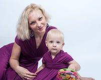 有一个小女儿的白肤金发的妇女匹配的穿戴 图库摄影