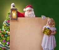 有一个小女孩、葡萄酒灯笼和海报的圣诞老人 免版税库存图片