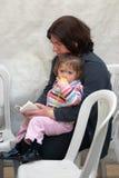 有一个小女孩的一名妇女祈祷在哭墙。 免版税图库摄影