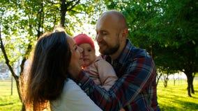 有一个小孩子的年轻家庭拥抱并且互相亲吻 父母亲父母拿着他们的他们的胳膊的女儿在 库存照片