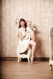 有一个小孩子的母亲内部的 在的微笑的家庭 图库摄影