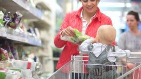有一个小孩的年轻女人推车购物的在超级市场 菜和草本,在包裹的沙拉的部门 股票录像