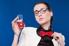 有一个小瓶的女孩在他的手和一只红色蝴蝶上在她的脖子 免版税库存图片