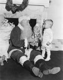 有一个小男孩和一个玩具熊的圣诞老人在火地方前面(所有人被描述不是更长生存和没有庄园 库存照片
