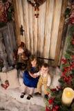 有一个小男孩的一个女孩坐与圣诞节12月的门廊 免版税库存图片