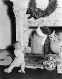 有一个小男孩的圣诞老人在壁炉前面(所有人被描述不更长生存,并且庄园不存在 供应商 库存图片