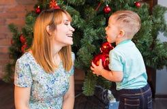 有一个小男孩的愉快的母亲在圣诞树附近 礼品新年度 库存图片