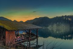 有一个小的码头的湖房子在山前面 免版税库存图片