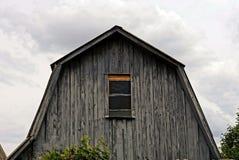 有一个小窗口的灰色木顶楼在天空背景 库存照片