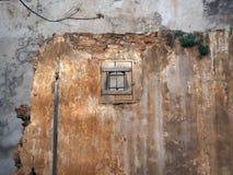 有一个小窗口的老墙壁 库存照片