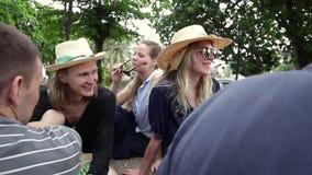 有一个小组年轻行家的人民坐在公园和交谈 股票录像