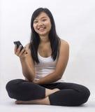 有一个巧妙的电话的亚裔女孩 库存照片