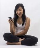 有一个巧妙的电话的亚裔女孩 库存图片
