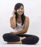 有一个巧妙的电话的亚裔女孩 免版税库存图片