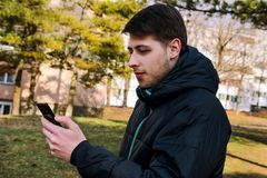 有一个巧妙的电话的人使用在公园 图库摄影