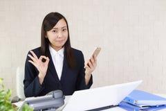 有一个巧妙的电话的女商人 免版税库存照片