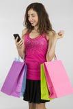 有一个巧妙的电话的购物妇女 库存照片