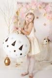 有一个巨大的圣诞节球的逗人喜爱的微笑的blondy女孩 库存照片