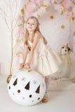 有一个巨大的圣诞节球的逗人喜爱的微笑的blondy女孩 免版税图库摄影